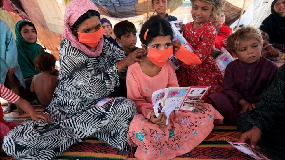 An internally displaced woman helps a girl put on a face mask distributed by Unicef
