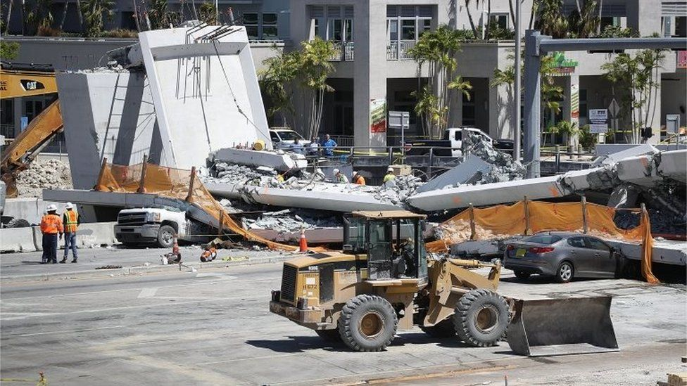 Law enforcement and members of the National Transportation Safety Board investigate the scene where a pedestrian bridge collapsed a few days after it was built in Miami, Florida.