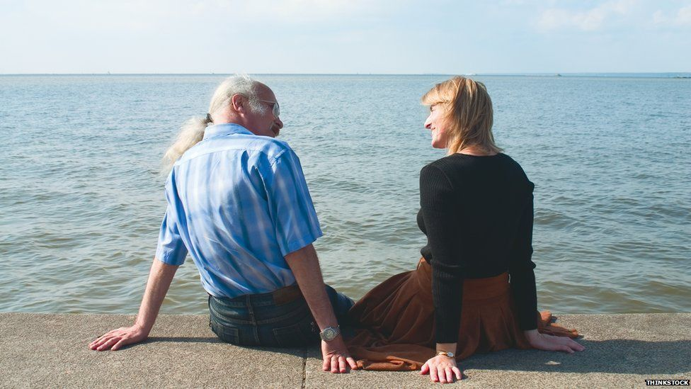 Couple talking, sitting by the seaside