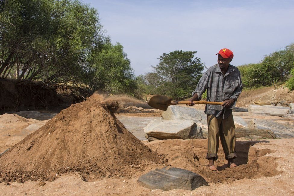 Sand harvester Richard Mutinda, 40, shovels sand into a big pile to be collected by trucks later that day. 100 tonnes of sand can be taken a day from this stretch of the Nthange River alone. There are 15 - 20 harvesting sites on this river.