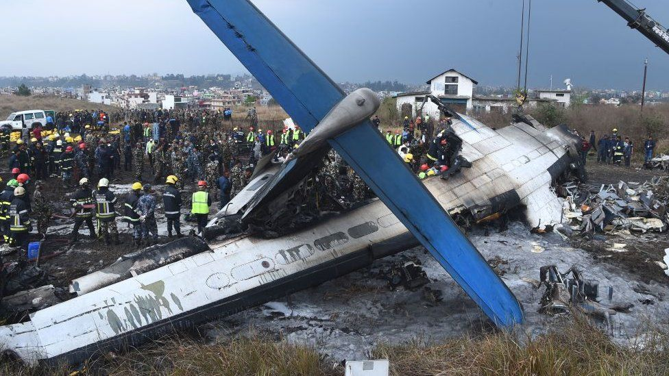 Nepali rescue workers gather around the debris of an airplane that crashed near the international airport in Kathmandu