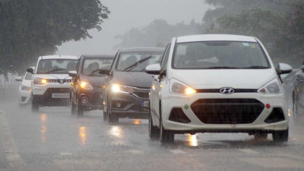 Commuters, motorist and vehicles are seen on the road amid rain in India on 5 October 2020.