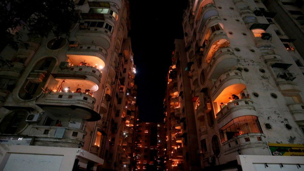 People stand on their balconies and light candles and oil lamps in India