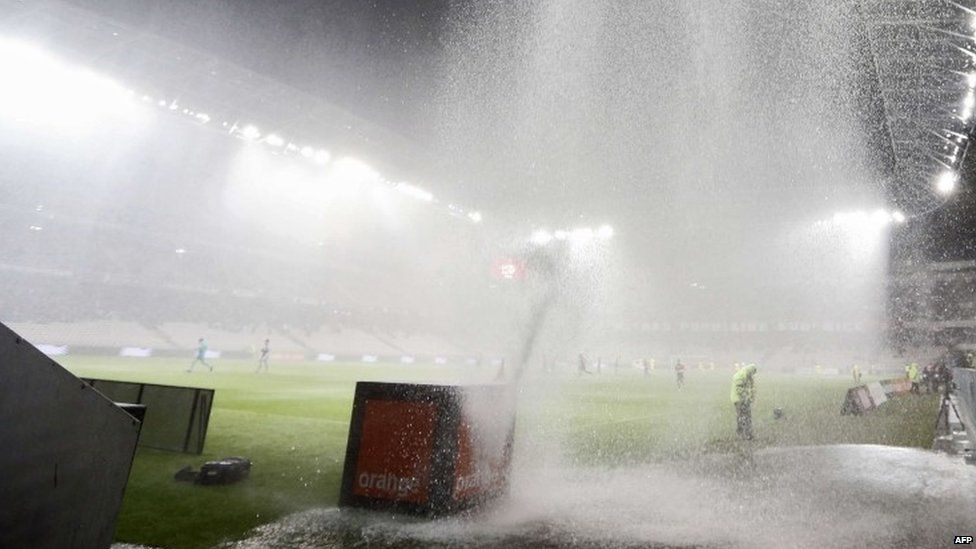 A football game in France is interrupted by heavy rain