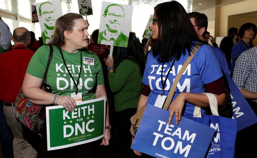 A supporter of Keith Ellison dressed in green and a supporter of Tom Perez dressed in blue speak to each other during a Democratic National Committee forum in Baltimore, Maryland, U.S,