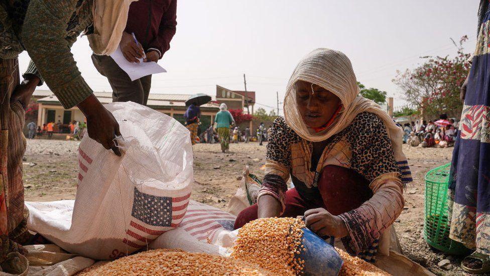 En hjælpearbejder distribuerer målte portioner af gule linser til beboere i Geha by