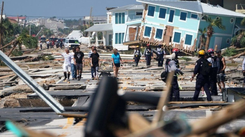 Mexico Beach residents walk down a street on Thursday
