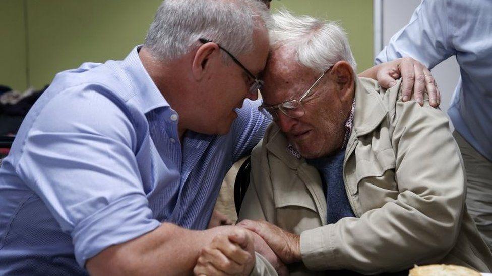 Australian PM Scott Morrison comforts Owen Whalan, a NSW resident who was evacuated