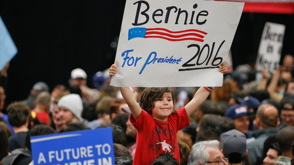 A child holds a sign supporting Democratic presidential candidate Sen. Bernie Sanders, I-Vt., while awaiting his arrival at the San Diego Convention Center