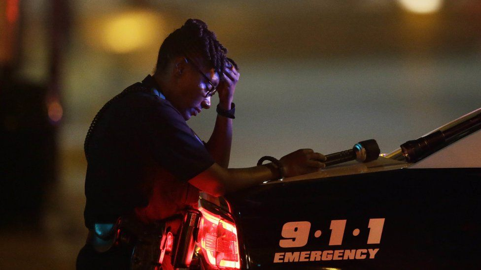 A Dallas police officer, who did not want to be identified, takes a moment as she guards an intersection in the early morning after a shooting in downtown Dallas, Friday, July 8, 2016