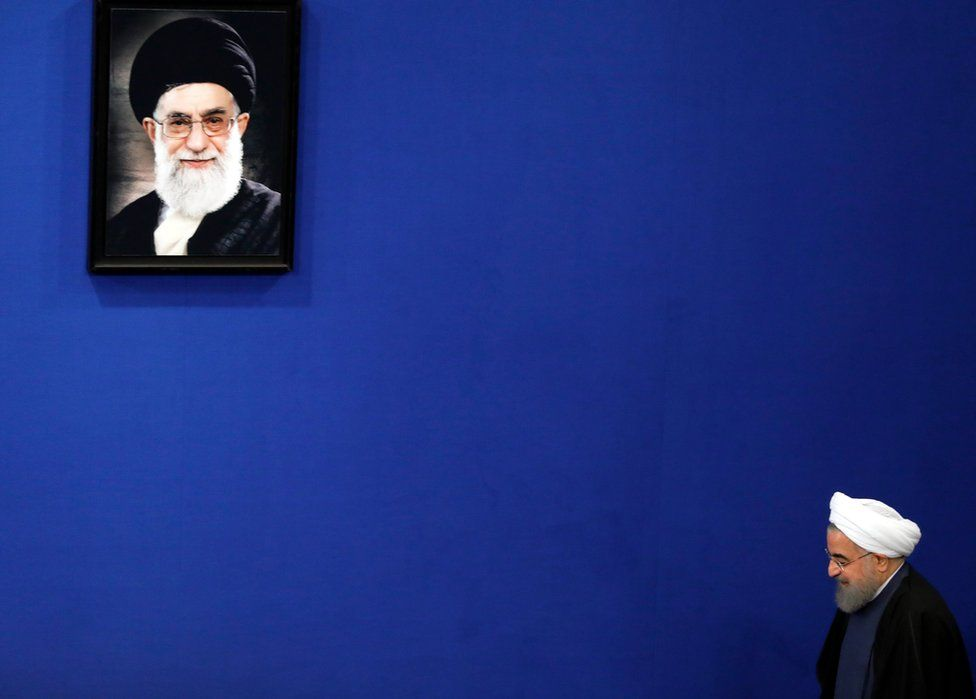 Iranian President Hassan Rouhani arrives, next to the picture of Iranian supreme leader Ali Khamenei, for a press conference in Tehran