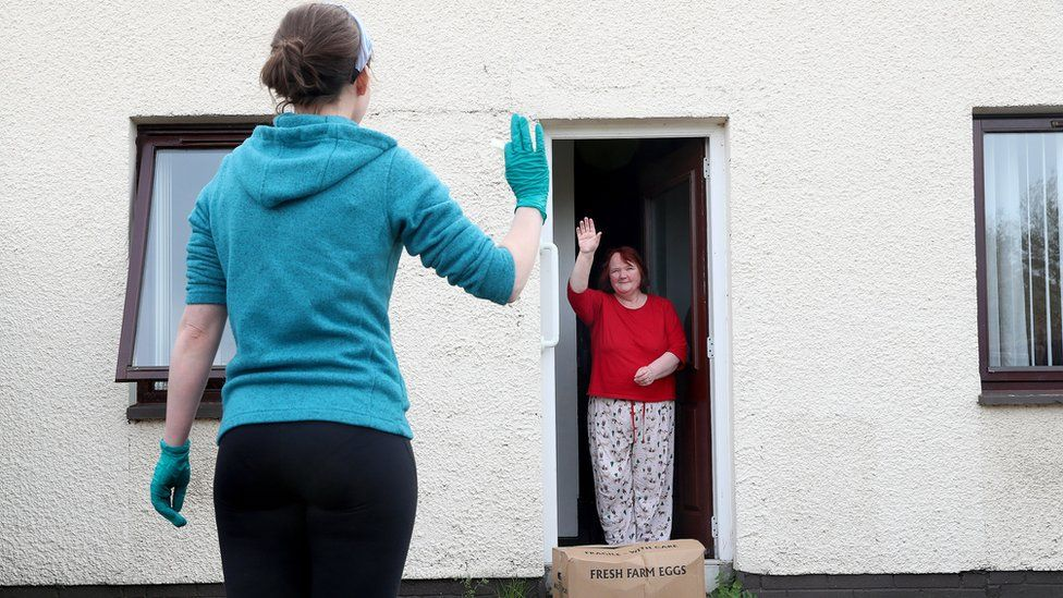 A volunteer delivers a food box to a lady in County Antrim