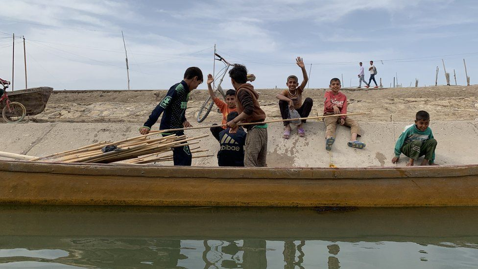 Children on a waterway bank smiling and waving