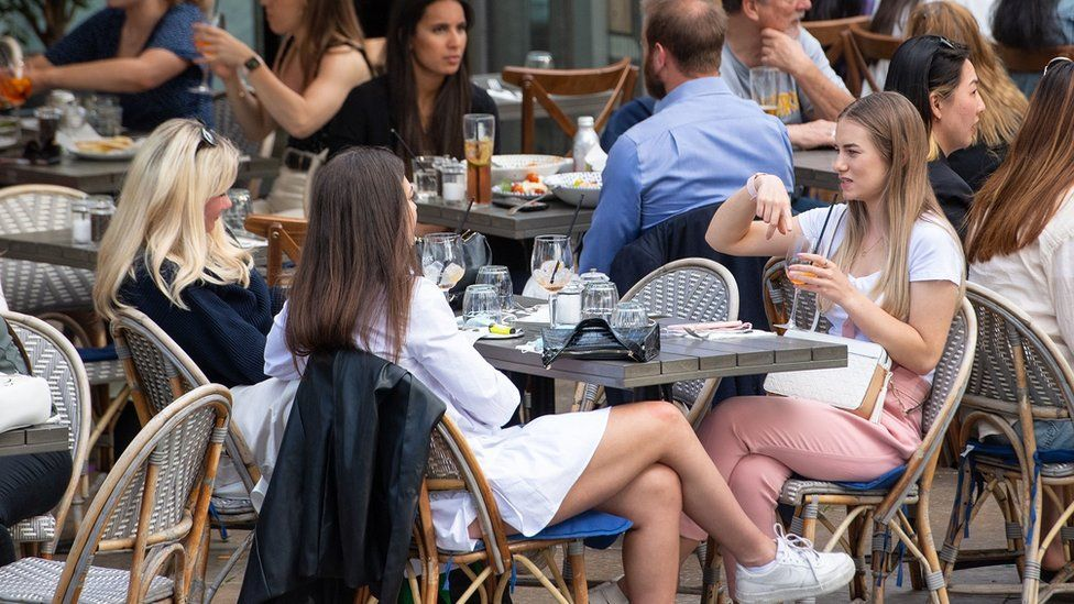 Women eat and drink at outside tables as they enjoy the warm weather on the South Bank in central London