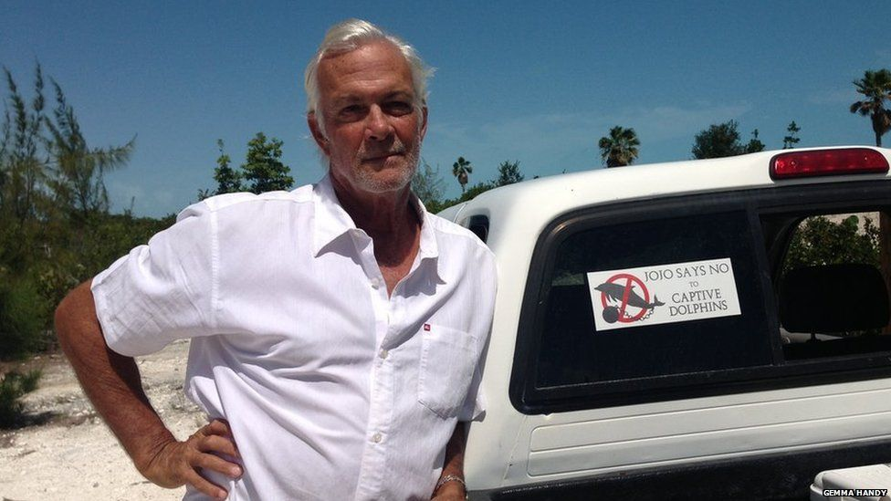 """Tim Ainley stands next to his car with a bumper sticker reading """"Jojo says no to captive dolphins""""."""