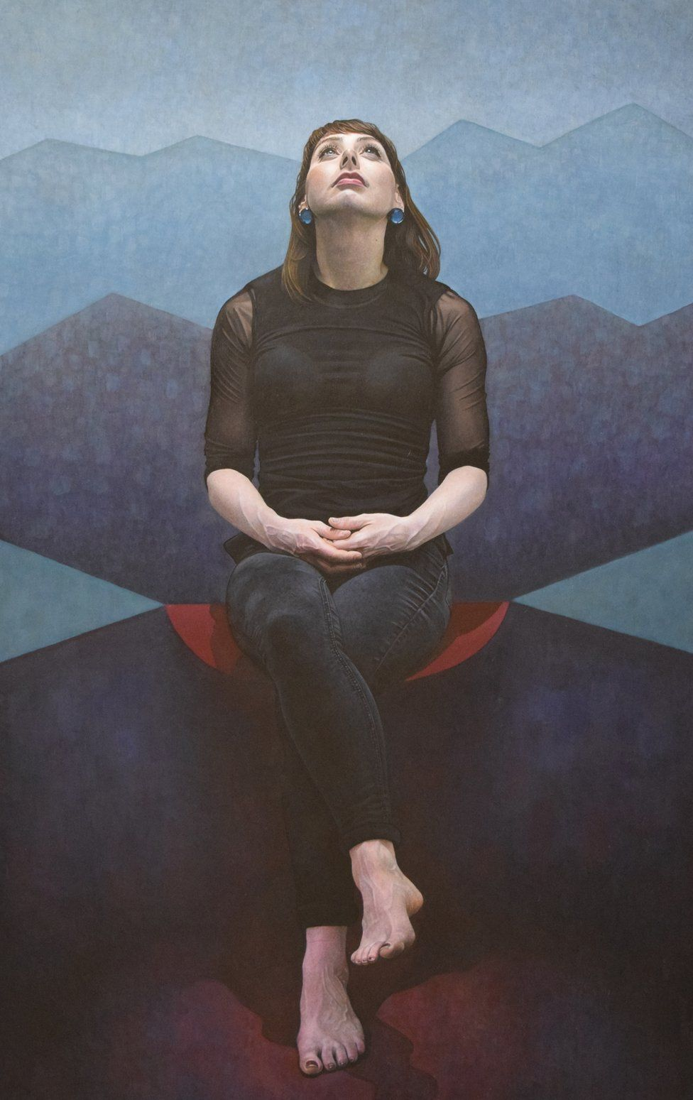Portrait Of A Woman Sat Looking Up With Her Legs Crossed