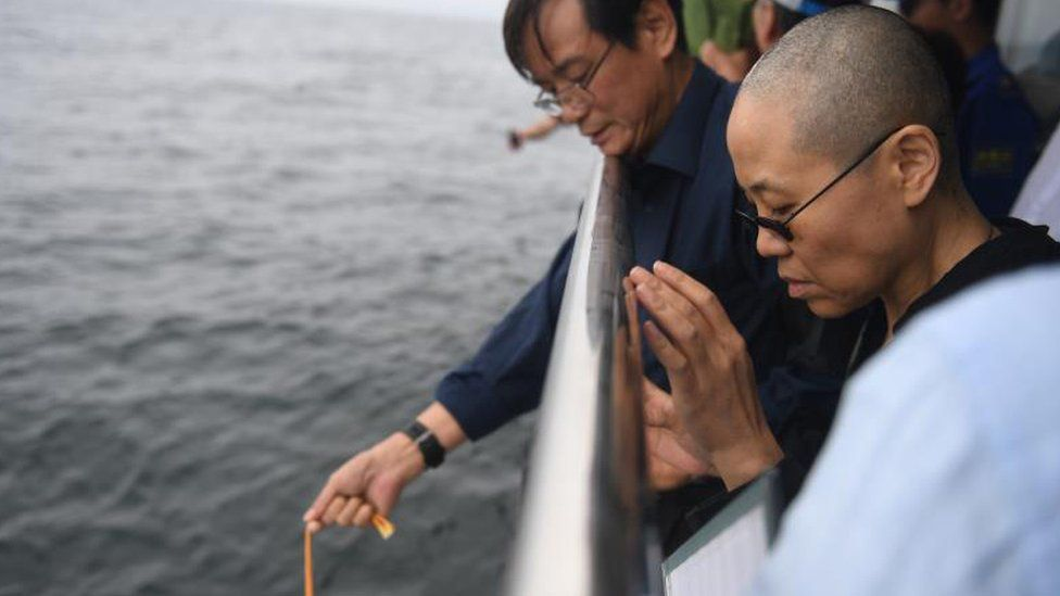 Liu Xiaobo's wife Liu Xia (R) prays as his ashes are scattered in the sea near Dalian