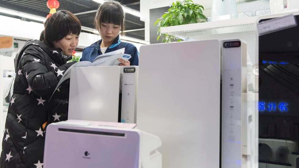 Shoppers look at air purifiers in Beijing