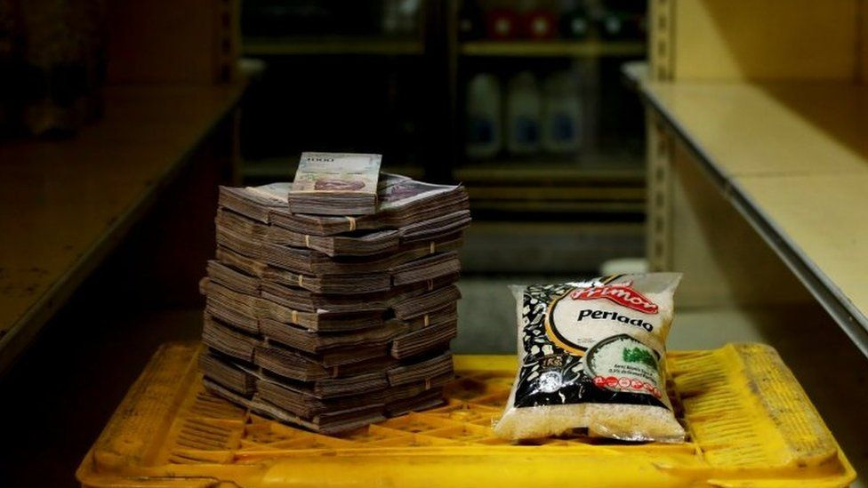 A package of 1kg of rice is pictured next to 2,500,000 bolivars, its price at a mini-market in Caracas, Venezuela