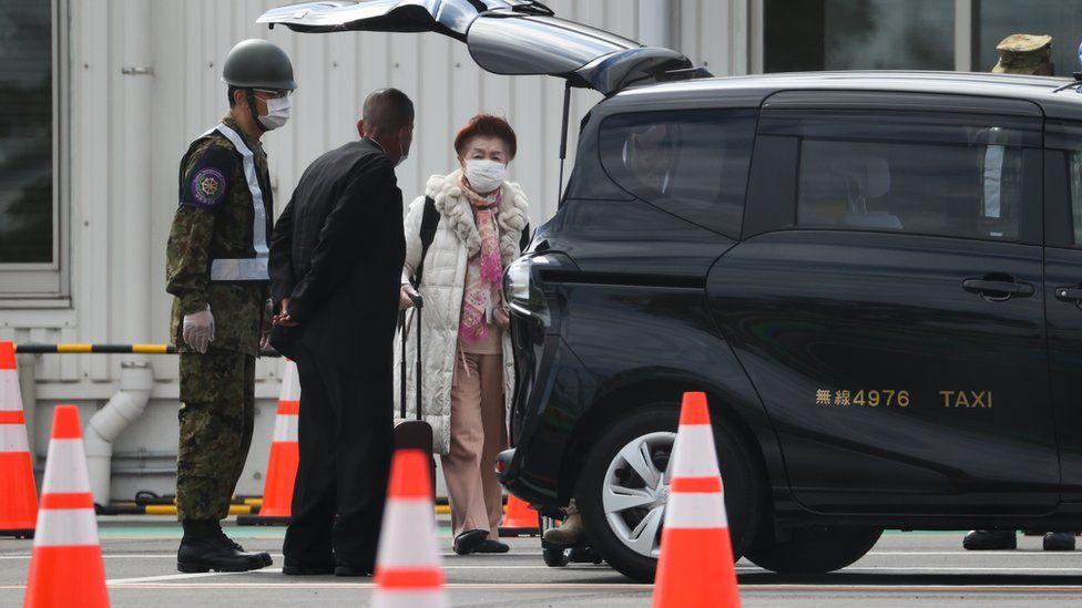 A passenger of the Diamond Princess cruise ship leaves Daikoku Pier on February 19, 2020 in Yokohama, Japan.