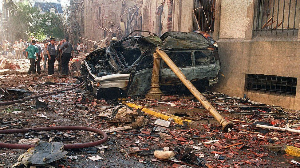 Police and rescue workers stand near destroyed cars and debris on March 17, 1992 in Buenos Aires shortly after a powerful bomb ripped through the Israeli Embassy