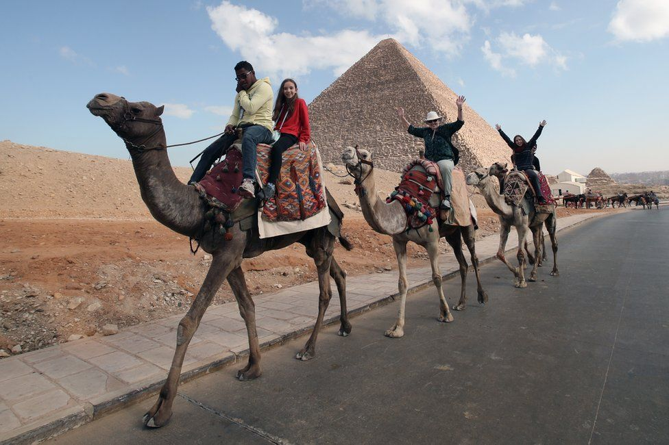 Tourists ride on camels in front of the Giza Pyramids, in Giza, Egypt, 26 December 2018
