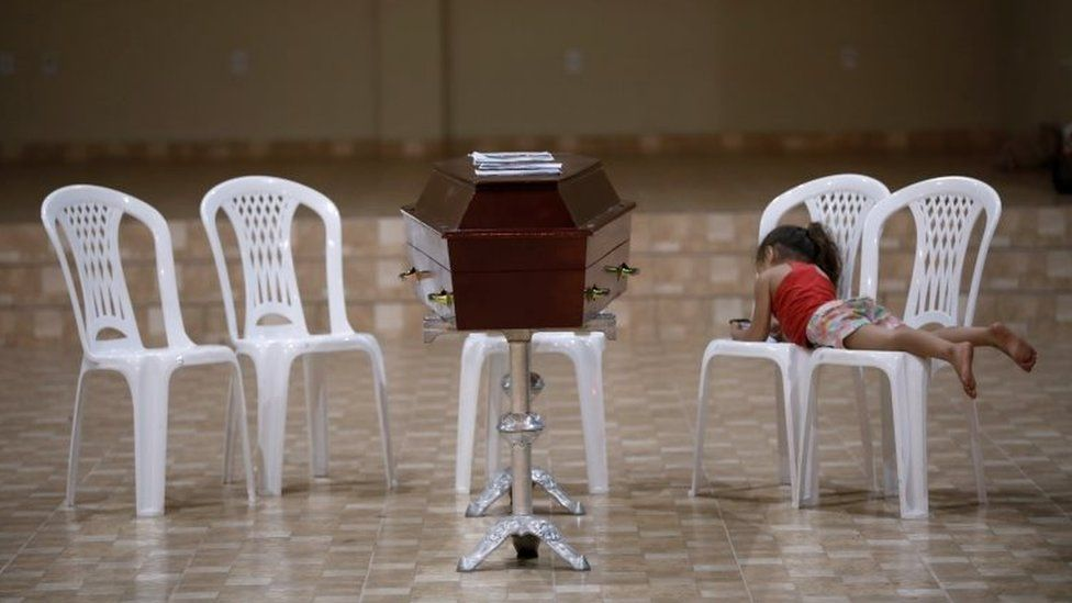 A relative of murdered prisoner lies on a chair next to a coffin during a wake after a prison riot in the city of Altamira, Para state, Brazil July 30, 2019.