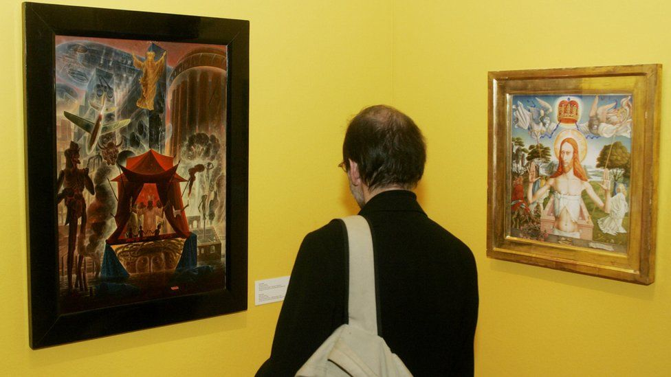A visitor looks at paintings of Austrian artist Ernst Fuchs at the Jewish Museum in Vienna, Austria.
