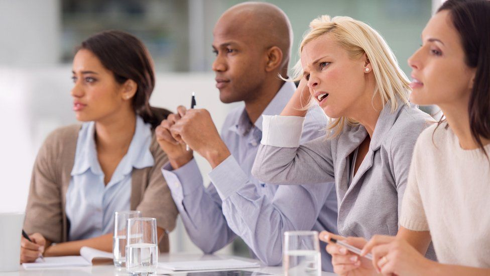 Businesswoman looking confused during a meeting with her colleagues