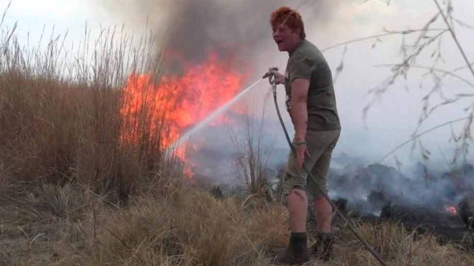 Bernadette Hall puting out a bush fire in South Africa