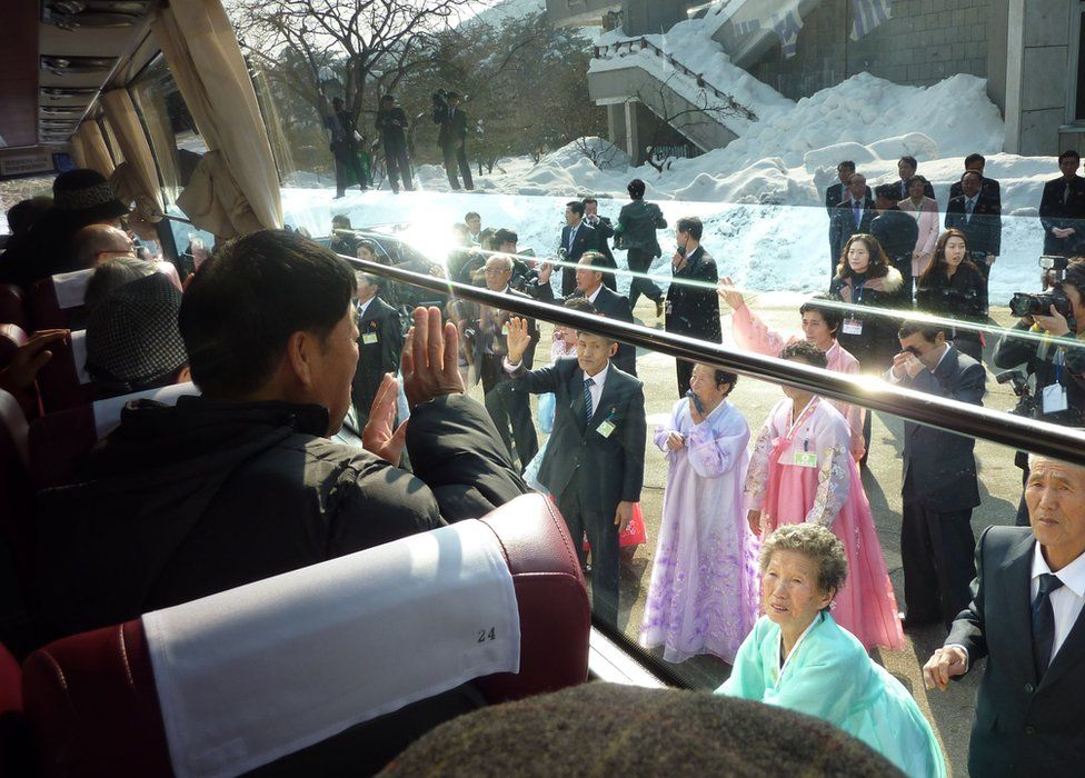 In a file photo taken on 22 February 2014 a South Korean man (L) waves to his North Korean relatives from the window of a bus following a family reunion at the resort area of Mount Kumgang, North Korea