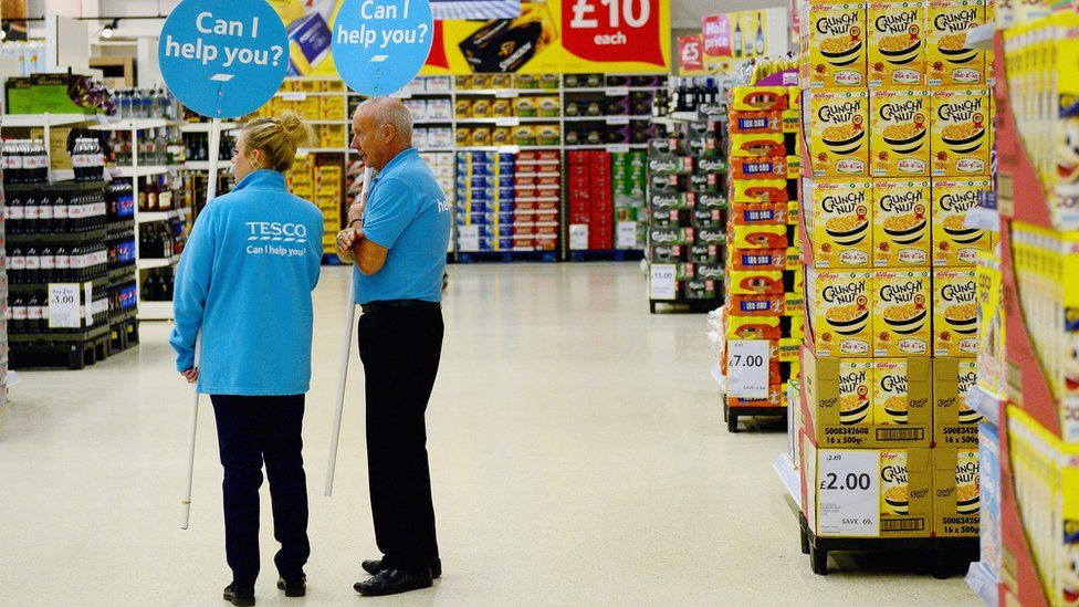 Two staff-members in a Tesco store