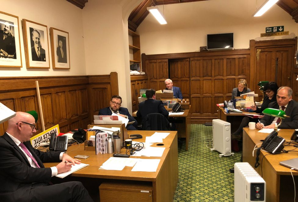 Mark Tami (rear) sitting in the Labour Whips office in the House of Commons