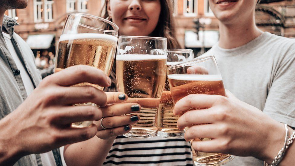 people holding beer glasses