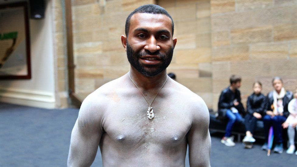 "Kalo, one of four ""mud men"" in Sydney for the exhibition, is a young man with white painted chest and a pendant"