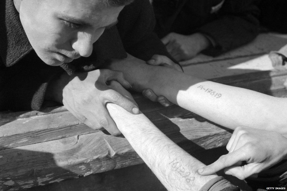 A young man checks the numbers tattooed on the arms of Jewish Polish prisoners coming from Auschwitz, in Dachau concentration camp after its liberation by the US army at the end of April 1945