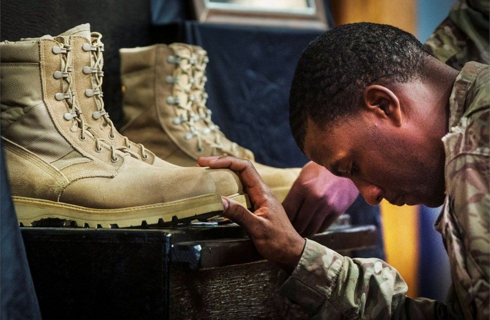 A US soldier from the 3rd Cavalry Regiment pays his respects during a memorial for Specialist Wyatt Martin and Sergeant First Class Ramon Morris at Bagram Air Field in Afghanistan, on December 23, 2014