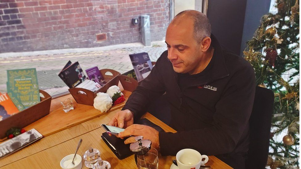 Facebook group moderator Jason Lawal on his phone