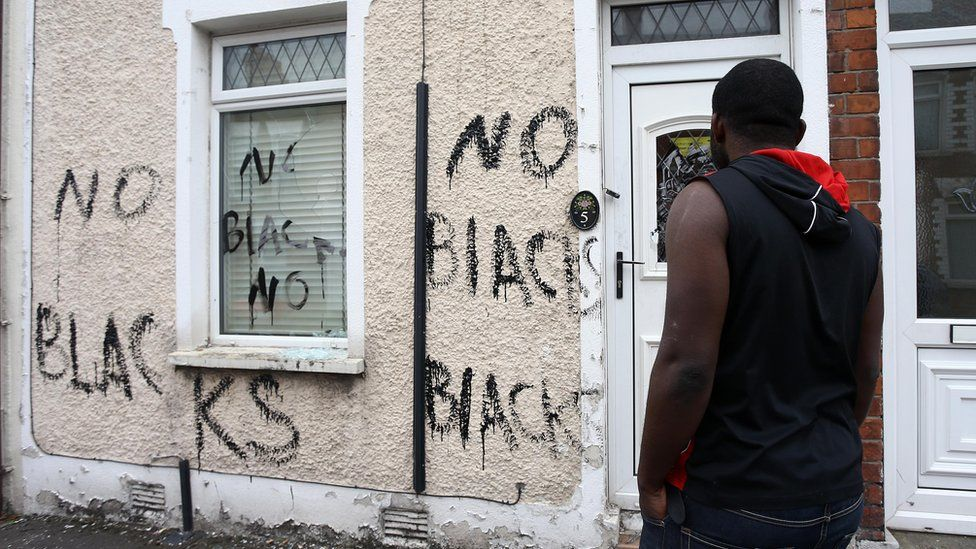 A man looks at racist graffiti on his house