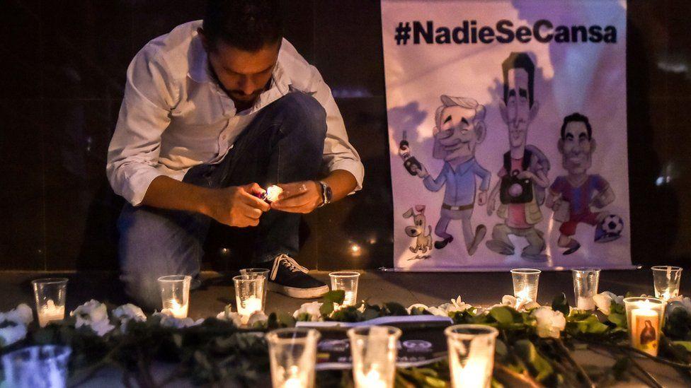 A journalist lights a candle for slain Ecuadorians