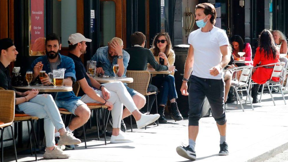 Man walking past people drinking outside a bar