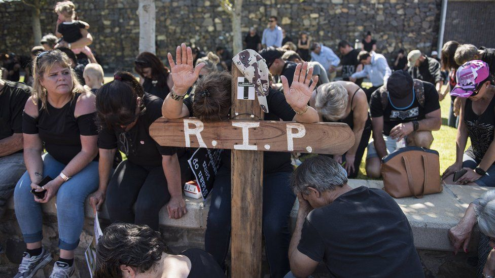 A white protester leans on a cross while others kneel on the ground to protest farm murders in South Africa.