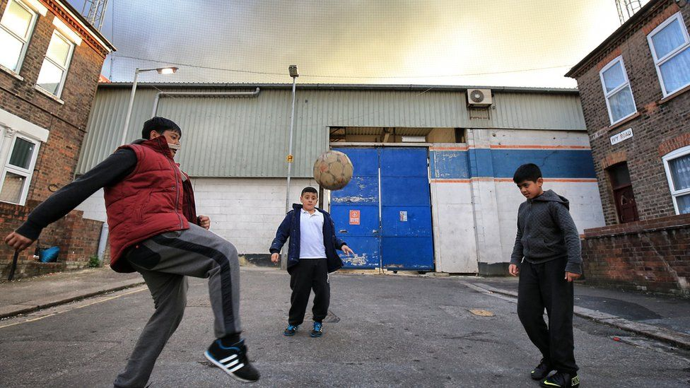 Boys play football in the shadow of Kenilworth Road