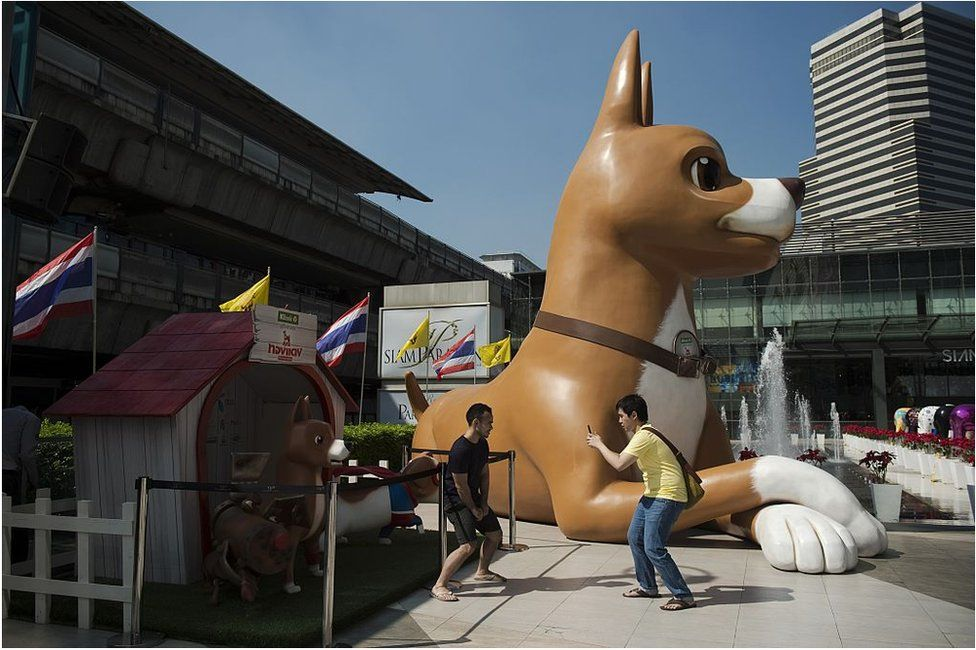 This photo taken on 9 December 2015 shows two men taking pictures with their smartphones next to a 10-metre high sculpture of 'Giant John', one of the characters of the film 'Khun Tongdaeng: The Inspirations', outside a shopping mall in Bangkok.