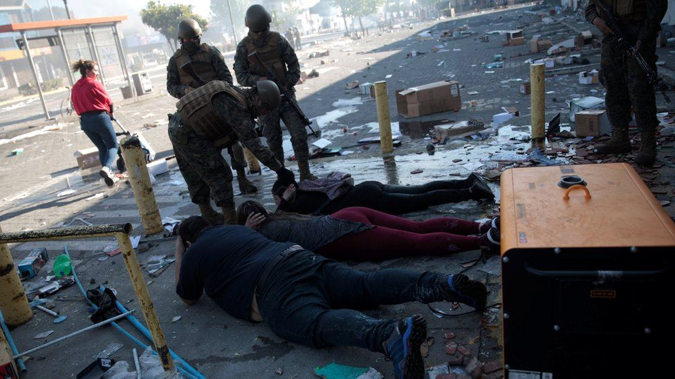Security forces detain suspected looters during a protest against high living costs, in Concepcion, Chile October 21, 2019