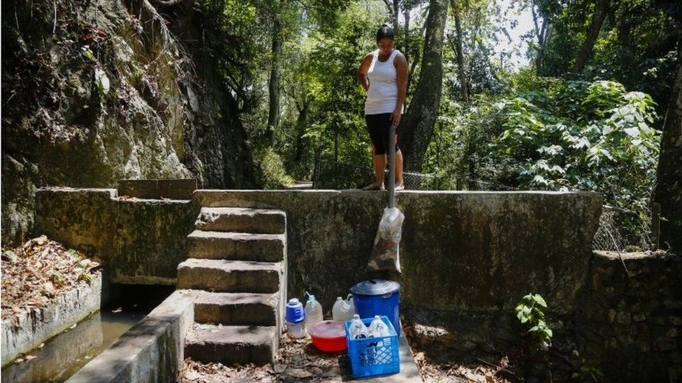 A woman looks at bottles and buckets filled with water from the mountain during blackouts, which affects the water pumps on March 12, 2019 in Caracas, Venezuela