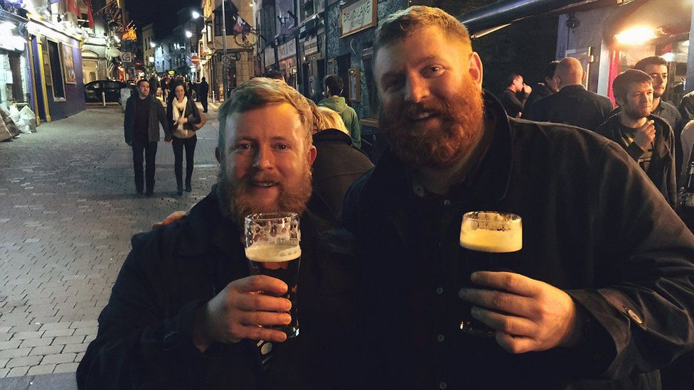 Two men who look very similar drinking pints of beer together.