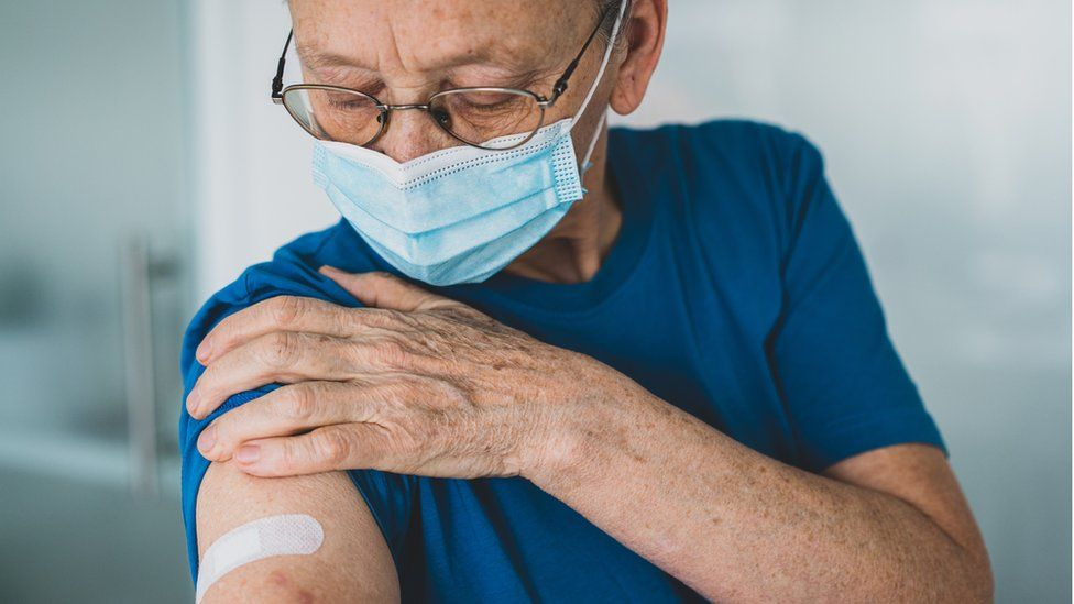 old woman looking at arm after vaccine