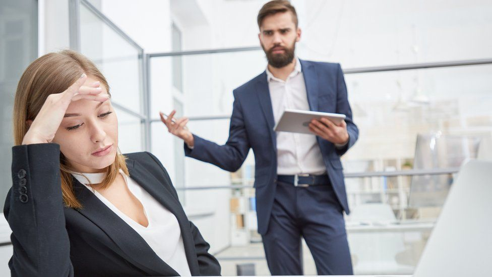 man arguing in an office with woman