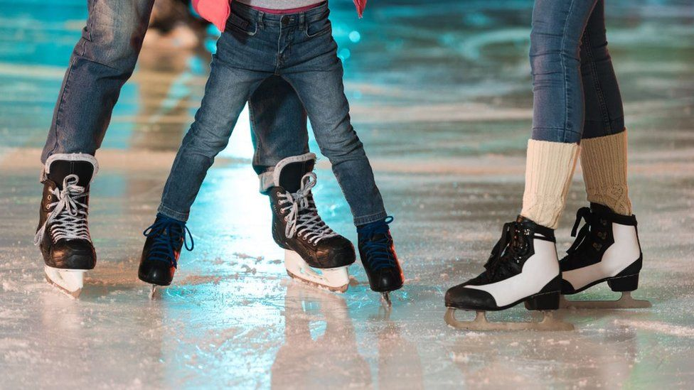 Three people on an ice rink with ice skates